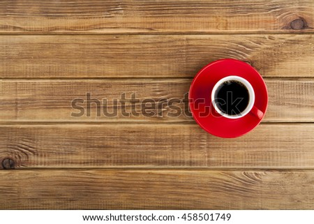 red cup with coffee on a wooden background