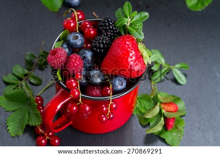 red cup with fresh ripe berries and leaves on black stone background, low key - stock photo