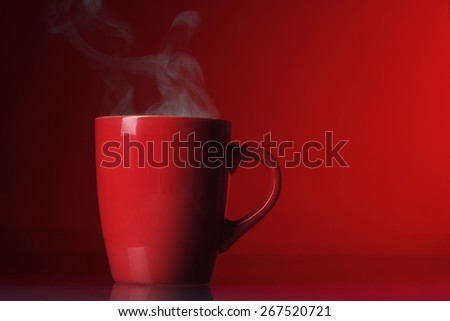 Red cup with steam over red background - stock photo