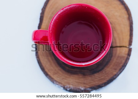 Red cup with tea on a wood slice in snow. Romantic winter picnic, hot tea. Lifestyle, time together outdoors. Copy space.