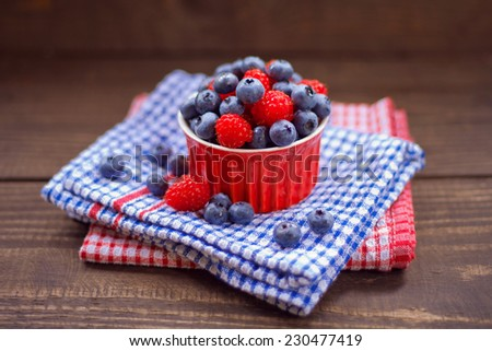 Red cup with wild fruits like blueberry and raspberry. All on the blue and red background.all and background berries berry blue blueberry board braided cake cup dessert  forest fruit l  red sweets  - stock photo