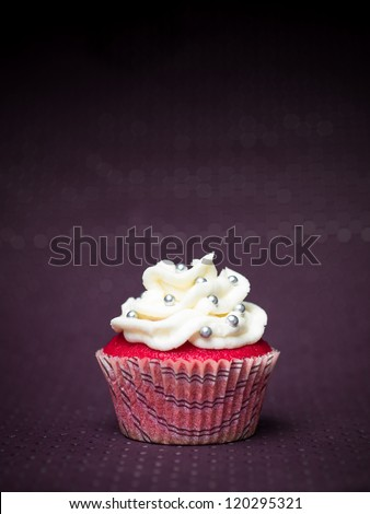 red cupcake with white icing and sprinkles silvery purple abstract background with dots - stock photo