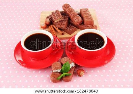 Red cups of strong coffee and chocolate bars on polka dot background