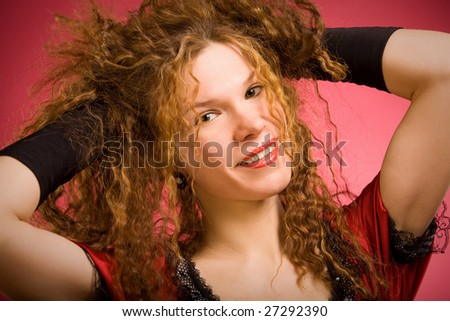 Red curly hair girl in red dress - stock photo