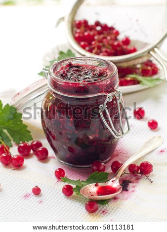 Red currant and black currant jam in jam-jar on dirty towel