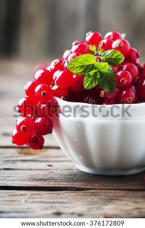 Red currant and mint on the wooden table, selective focus