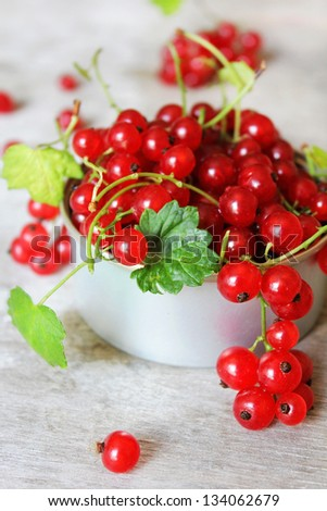 Red currant berries with green leaves in a cup on a wooden surface - stock photo