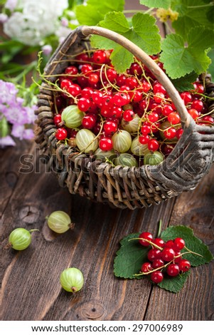 Red currant, gooseberry in the basket on wooden background