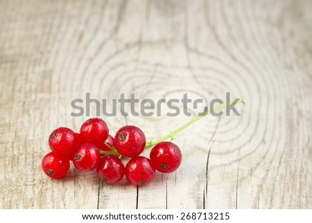 Red currant on a wooden table, rustic kitchen - stock photo