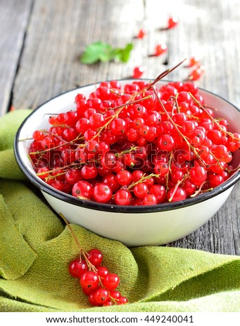 Red currants in a cup on a wooden dark style Rustic style