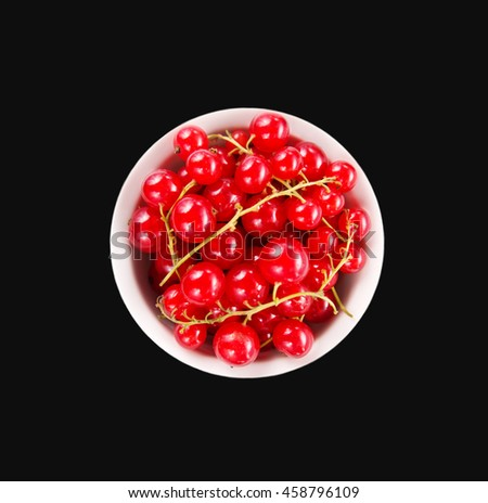Red currants in the bowl. Ripe and tasty currant isolated on black background. - stock photo