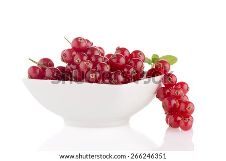 Red Currants on white ceramic bowl close up on white background.