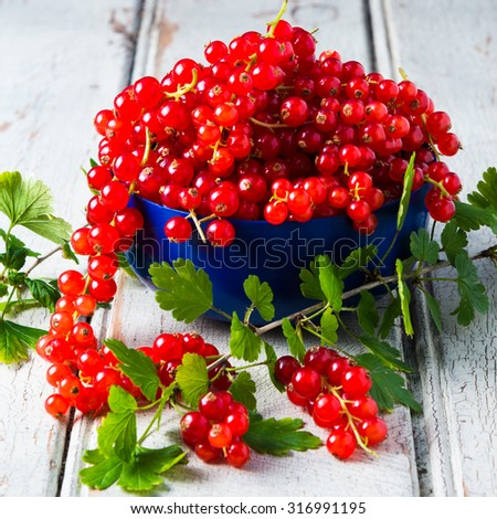Red currants with leaves on old wooden background, selective focus - stock photo