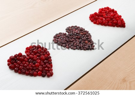 Red current, cranberries and beans in heart shape on wooden board with copy space, horizontal view, selective focus - stock photo
