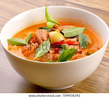 Red curry with roast duck on wooden background