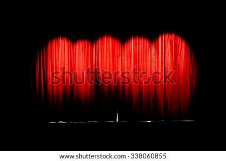 Red curtain of movie theater closed illuminated by 5 spot lights - stock photo