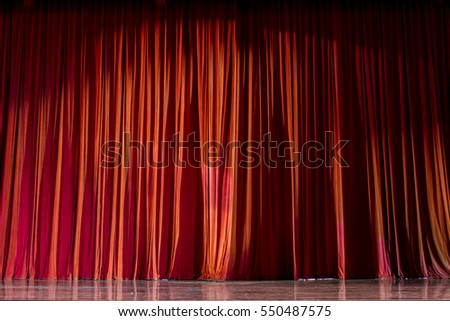 Red curtains and the wooden stage in a theater.