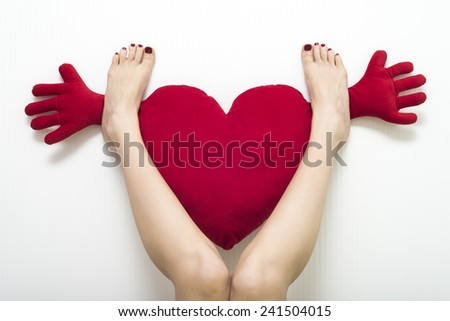 red cushion on formed heart and  female bare foot - stock photo