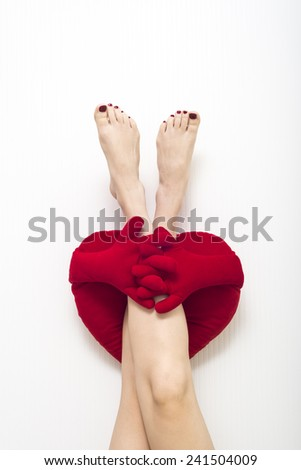 red cushion on formed heart hug female bare foot - stock photo
