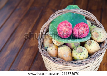 Red cut in half prickly pear on a cactus leave and a wicker basket full of just picked prickly pears on a wooden table - stock photo