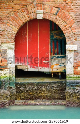 Red damaged door at a Venetian canal. - stock photo