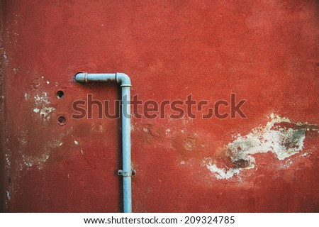 red damaged old wall with a pipe in the middle - stock photo