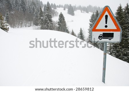 Red danger sign on road covered with snow - stock photo