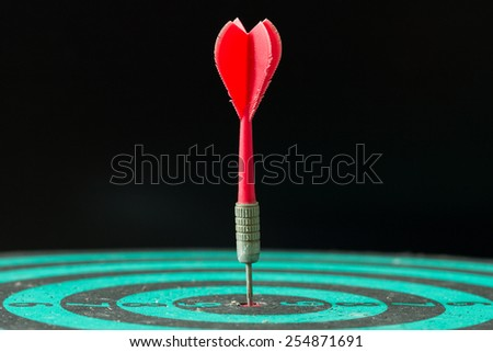 Red dart arrow hitting in the center of green dartboard. - stock photo
