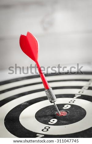 Red dart arrow hitting in the target center of dartboard - stock photo