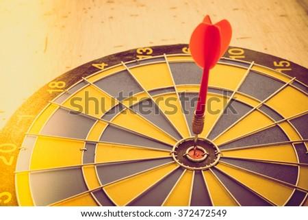Red dart arrow hitting on center of dartboard - Vintage light leak effect & selective focus - stock photo