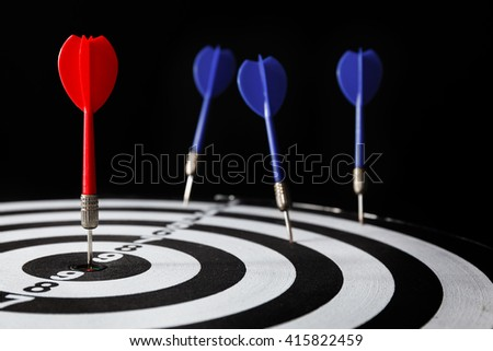 Red dart arrow on the target with dartboard, leadership concept, high contrast and dark lighting tone - stock photo