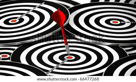 red dart hitting the center of a dartboard, there is may other targets around it - stock photo