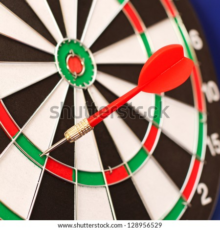 Red Dart in a Dart Board in narrow focus (Original image of the world is a public domain image from NASA) - stock photo