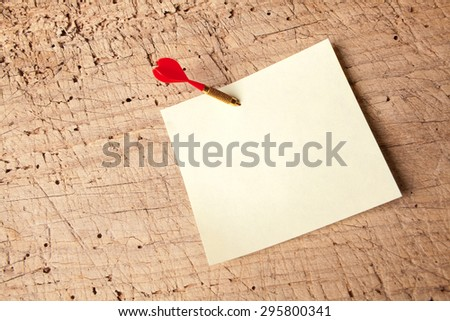 Red dart in an empty or blank notepad on a vintage wooden board - stock photo