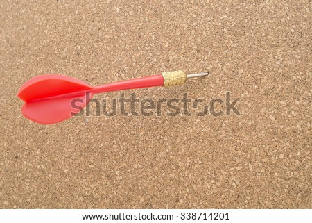Red dart on cork board. Concept of goal, targeted. Copy space for text. - stock photo
