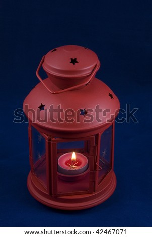 Red decorative lantern with a candle on a dark blue background - stock photo