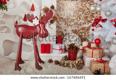 red deer near chimney with presenrts and white tree - stock photo