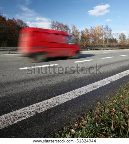 Red delivery/cargo van going fast on a highway - stock photo