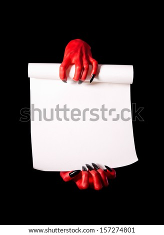 Red devil hands holding paper scroll, deal with devil concept, isolated on black background  - stock photo