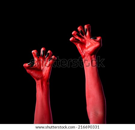 Red devil hands with black nails, Halloween theme, isolated on black background  - stock photo