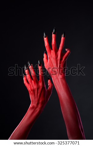 Red devil hands with black nails reaching out, Halloween theme   - stock photo