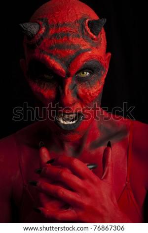 Red devil woman. Low key lighting. - stock photo