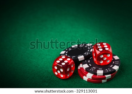 Red dice and chips on green table - stock photo