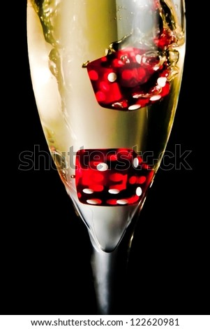 red dice dropping in the champagne flute on black background - stock photo