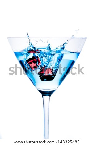 red dice falling in the blue cocktail glass with splashes on white background - stock photo