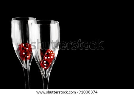red dice in a champagne glass on black background - stock photo
