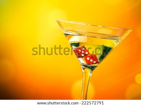 red dice in the cocktail glass on golden bokeh background - stock photo