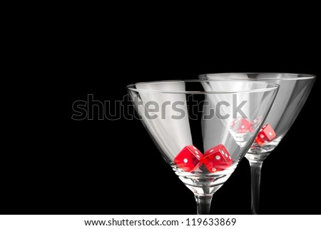 red dice in two cocktail glasses on black background with space for text - stock photo