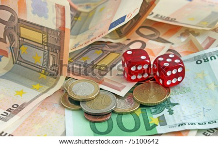 red dice on banknotes and coins