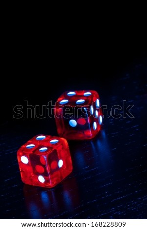 red dice on old wood black table on light blue tint background with space for text
